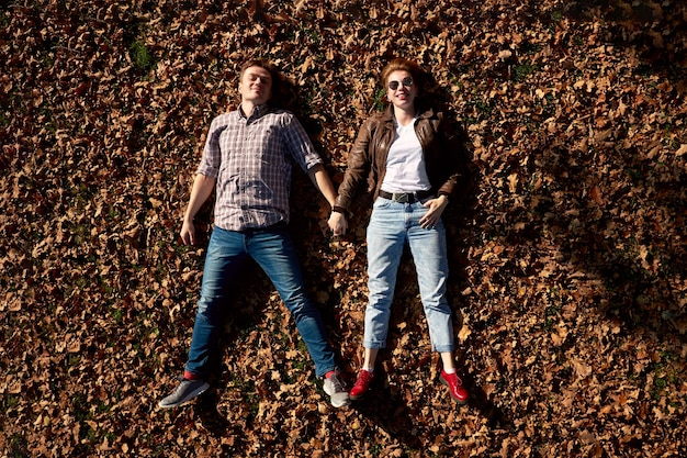 Happy positive young beautiful couple lying on the ground and holding hands in autumn park.