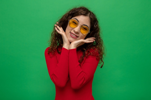 Happy and positive young beautiful woman in red turtleneck wearing yellow glasses  smiling cheerfully with hands on her face standing over green wall
