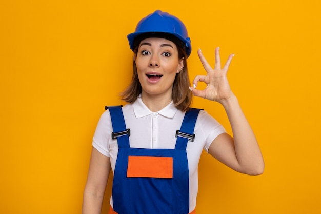 Happy and positive young builder woman in construction uniform and safety helmet looking smiling doing ok sign