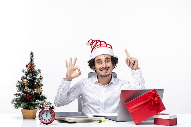 上を指し、白い背景の上のオフィスで眼鏡のジェスチャーを作る面白いサンタクロースの帽子と幸せなポジティブな青年実業家