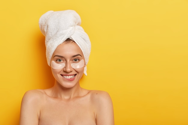 Happy positive young european woman bites lips, looks joyfully at camera, wears cosmetic patches under eyes, stands shirtless against yellow background, blank space