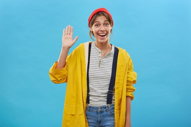 Happy positive young female dressed casually waving with her palm greeting friends, showing friendly sign isolated over blue wall. smiling pleasant-looking woman raising her hand with pleasure