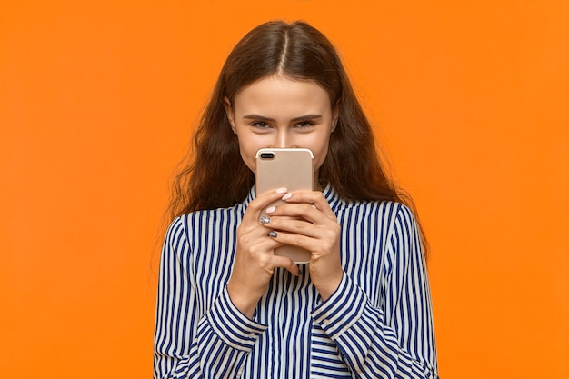 Felice giovane femmina positiva in camicia a righe tenendo il cellulare sul viso e fissando la fotocamera