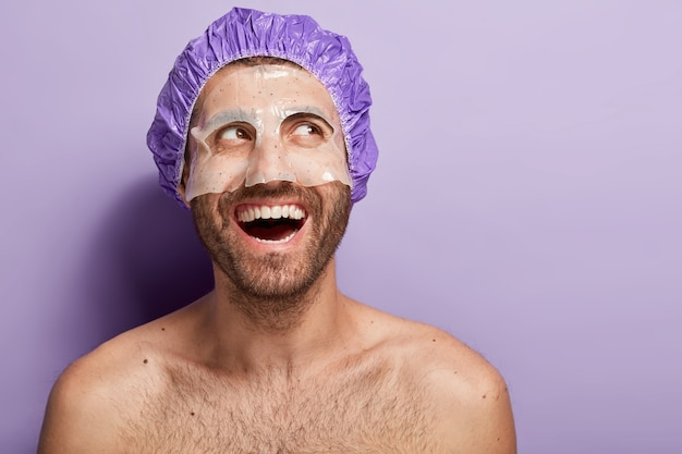 Il giovane positivo felice applica la maschera facciale, indossa la cuffia per la doccia, ride positivamente, ha il corpo nudo, setole scure, gode di un trattamento termale