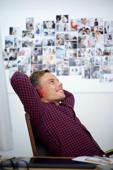 ディノ王が大きなプロジェクトに取り組んだ後、彼の肘掛け椅子に寄りかかってヘッドフォンで良い音楽を聴いている幸せなポジティブな若い男
