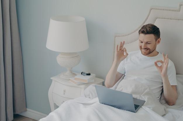 Счастливый позитивный молодой человек сидит в уютной постели после пробуждения рано утром, болтает по видеозвонку на ноутбуке и улыбается, соглашается с другом, соединяющим пальцы обеими руками в знаке ок
