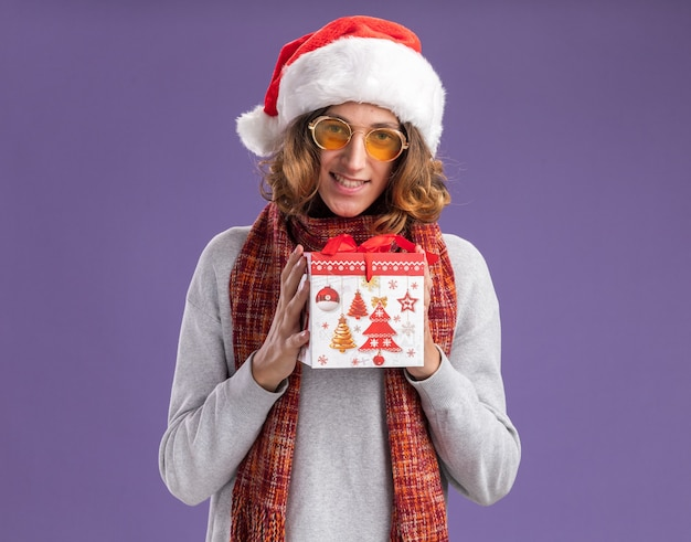 Happy and positive young man wearing christmas santa hat and yellow glasses with warm scarf around his neck holding christmas gift looking at camera with smile on face standing over purple background
