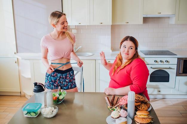 幸せな肯定的な若いしっかりした造りの女性はプラスサイズモデルを見て、笑顔します。腰周りはブルーのソフトテープ。退屈な不幸な脂肪モデルは振り返る。