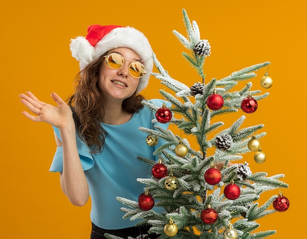Happy and positive young woman in blue top and santa hat wearing yellow glasses decorating christmas tree looking at camera waving with arm standing over orange background