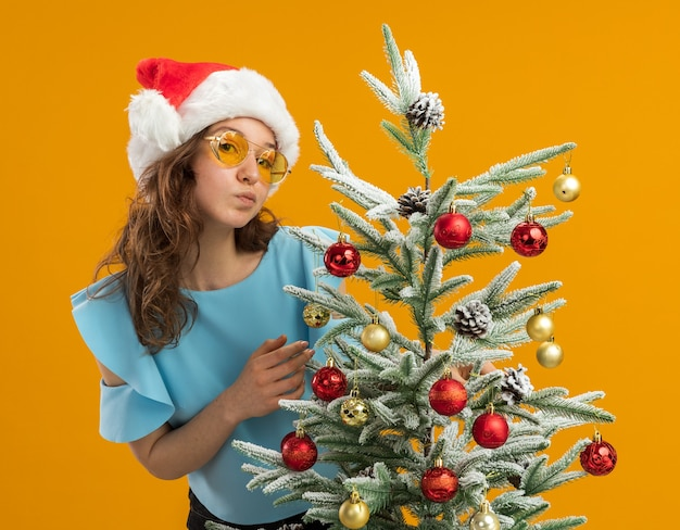Felice e positiva giovane donna in top blu e cappello da babbo natale che indossa occhiali gialli che decorano l'albero di natale in piedi sopra la parete arancione