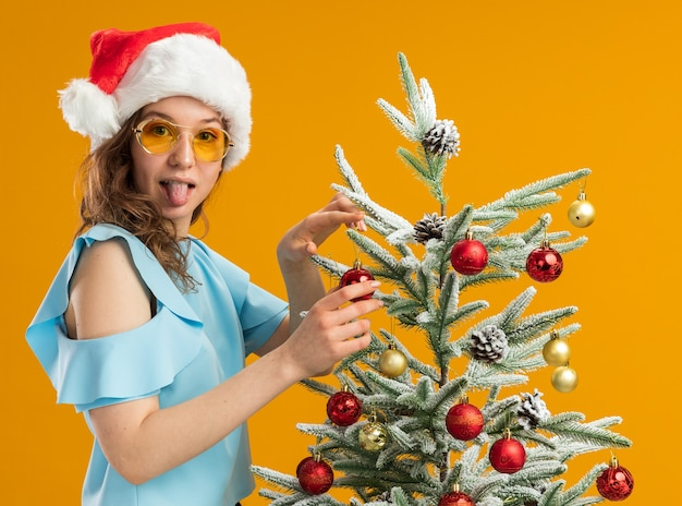 Happy and positive young woman in blue top and santa hat wearing yellow glasses decorating christmas tree sticking out tongue looking at camera standing over orange background