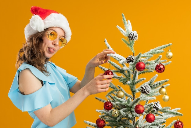 Happy and positive young woman in blue top and santa hat wearing yellow glasses   decorating christmas tree sticking out tongue standing over orange background