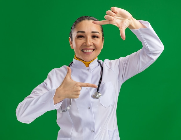 Felice e positiva giovane dottoressa in camice bianco con stetoscopio intorno al collo che fa un gesto di cornice con le dita in piedi sul muro verde