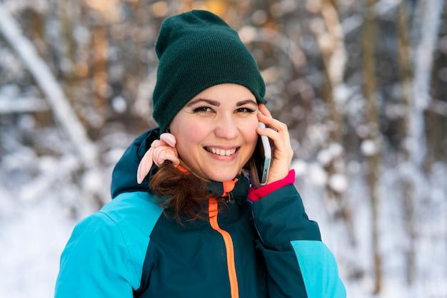 Счастливая позитивная молодая женщина гуляет в парке в зимний холодный солнечный день и разговаривает по мобильному телефону