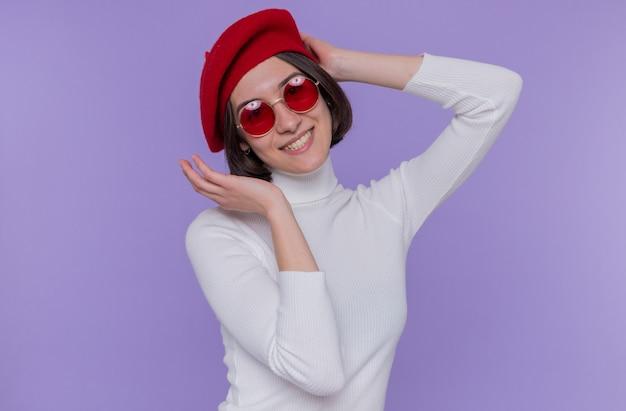 Felice e positiva giovane donna con i capelli corti in dolcevita bianco che indossa berretto e occhiali da sole rossi guardando la parte anteriore sorridente allegramente in piedi sopra la parete blu