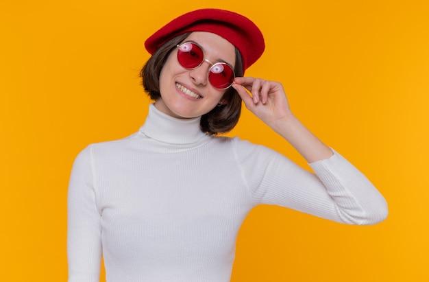 Felice e positiva giovane donna con i capelli corti in dolcevita bianco che indossa berretto e occhiali da sole rossi guardando la parte anteriore sorridente allegramente in piedi sopra la parete arancione