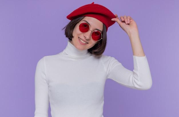 Felice e positiva giovane donna con i capelli corti in dolcevita bianco che indossa berretto e occhiali da sole rossi guardando davanti sorridente allegramente toccando il suo berretto in piedi sopra il muro blu