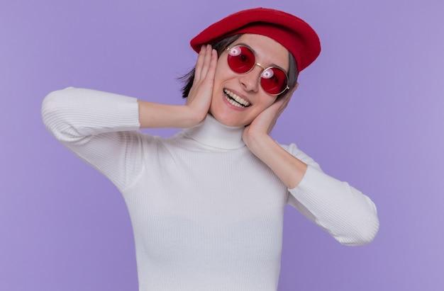 Felice e positiva giovane donna con i capelli corti in dolcevita bianco che indossa berretto