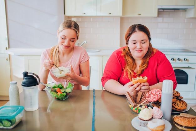 キッチンで幸せな肯定的な若い女性。スリムでしっかりとした作りのモデルは、サラダを食べて楽しめます。プラスサイズの若い女性は笑顔でジャンクフードを食べます。
