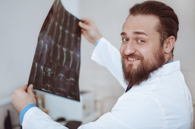 Happy practitioner examining x-ray scans of a patient