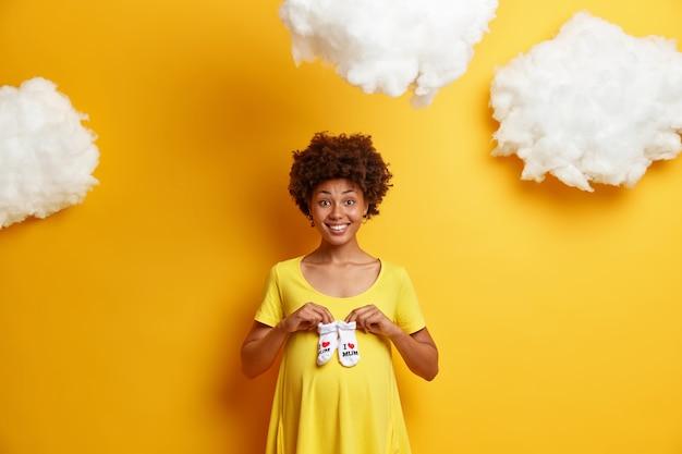 행복한 임신과 기대 개념. 웃는 미래의 임산부는 복부에 아기 옷 양말을 들고, 아이를 예상하고, 임신 중이며, 노란색 드레스를 입고, 푹신한 흰 구름 위에