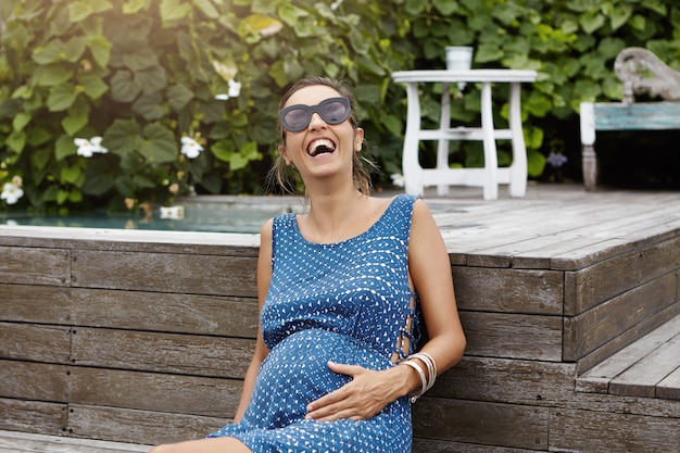 幸せな妊娠と出産の概念。新鮮な空気と外の暖かい天候を楽しんでいるサングラスをかけている若い妊娠中の女性、木の床のプールに座って、元気に笑っています。