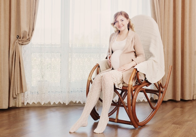 Happy pregnancy sitting on rocking chair at home