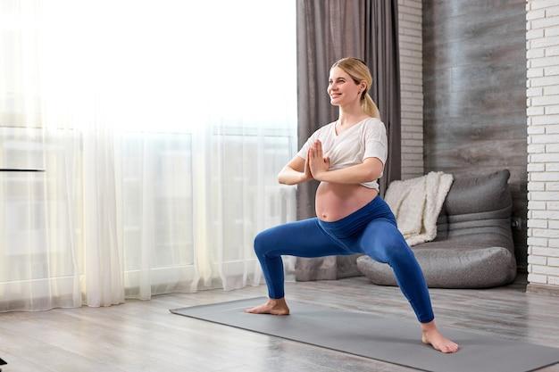 Happy pregnant caucasian woman training yoga at home
