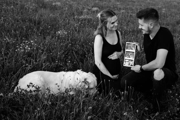 행복한 임신한 부부는 태어나지 않은 아이의 초음파 사진에 만족합니다. 흑백 사진입니다. 아이를 기다리고 있습니다. 임신 관리. 현대적인 검사 방법. 임신의 행복한 순간.