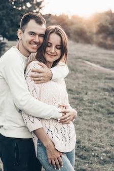 日没、妊娠中の女性の腹で幸せな妊娠中のカップル。夏のロマンチックな雰囲気の中で日没で手を繋いでいる妊娠中の女性とカップルします。
