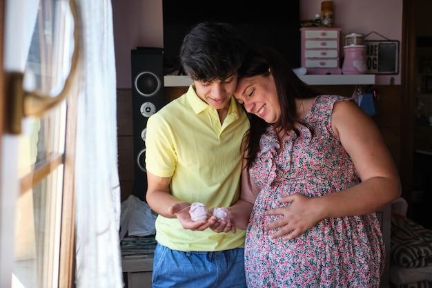 赤ちゃんのブーツを手に持って幸せな妊娠中のカップル