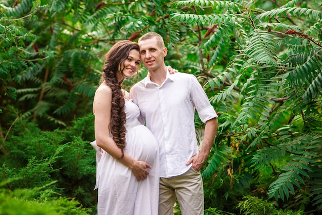 A happy pregnant couple is walking in nature.
