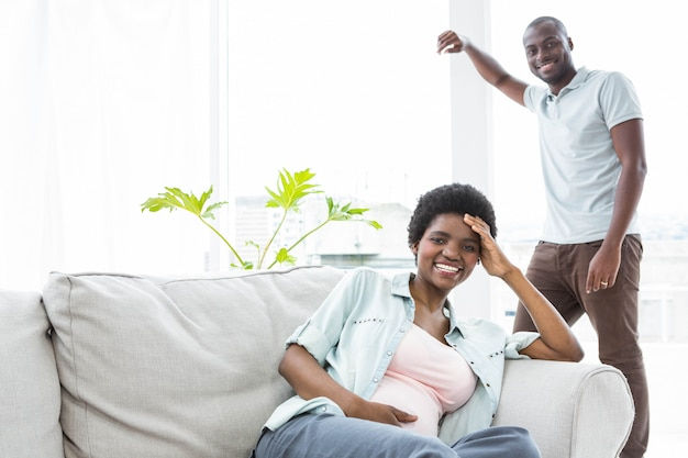 Happy pregnant couple in living room at home