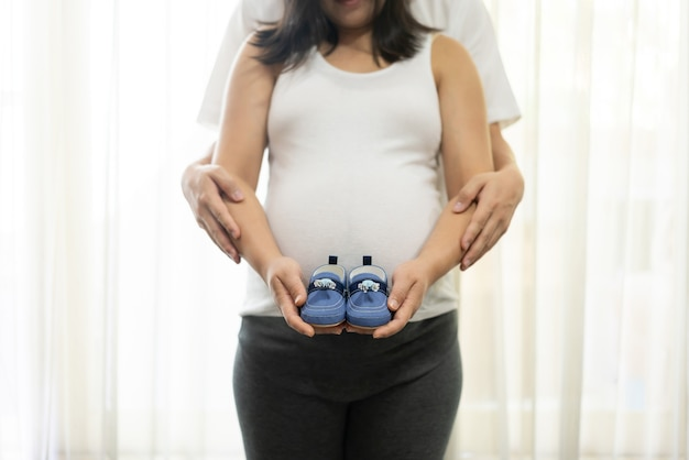 夫と妻の幸せな妊娠中のカップル。若い期待の女性は妊娠中の腹に赤ちゃんを抱きます。