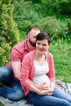 Счастливая беременная пара на открытом воздухе.