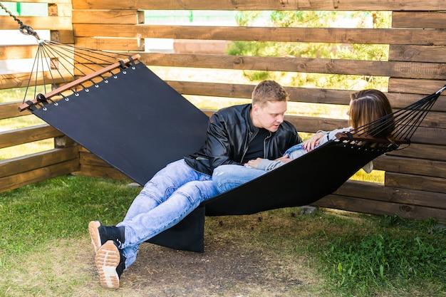 ハンモックに座っている幸せな妊娠中のカップル-家族、親子関係、幸福の概念。