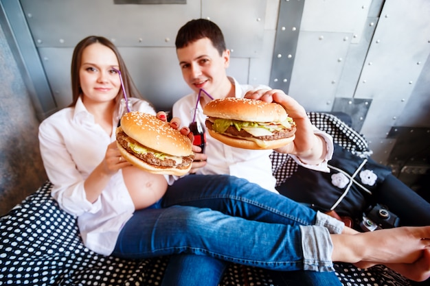 Happy pregnant family eating fast food