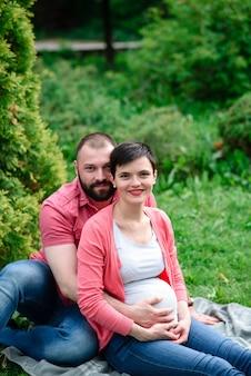 Счастливая беременная семья в парке