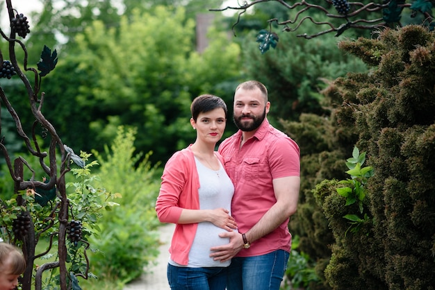 公園で散歩を話している幸せな妊娠中の家族