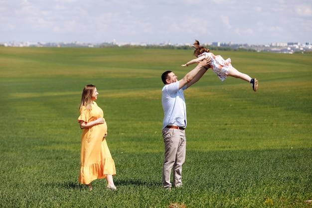 Счастливая беременная семья с маленькой дочерью, проводящей время вместе в солнечном зеленом поле в летний день