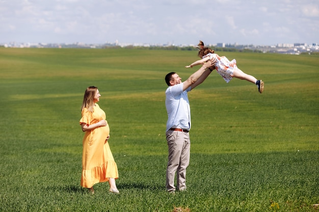 Happy pregnant family with little daughter spending time together in sunny green field on summer day