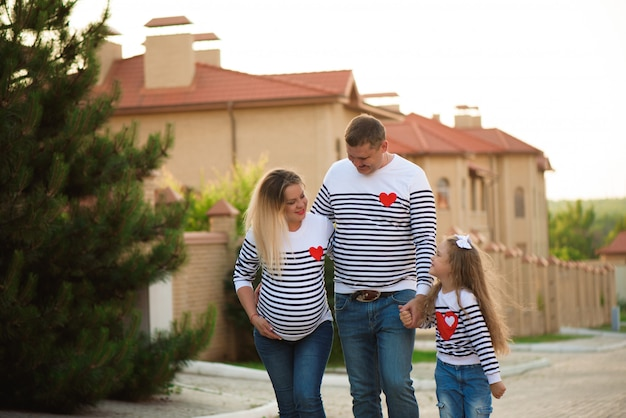 Happy pregnant family with little girl having fun walking summer time.