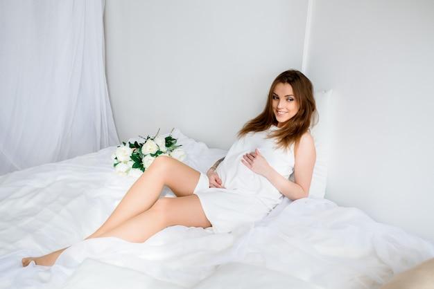 Счастливая беременная девушка в белом платье.