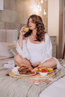 Счастливая беременная девушка сидит в позе лотоса и пьет апельсиновый сок