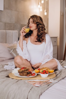 Happy pregnant girl sits in lotus position and drinks orange juice