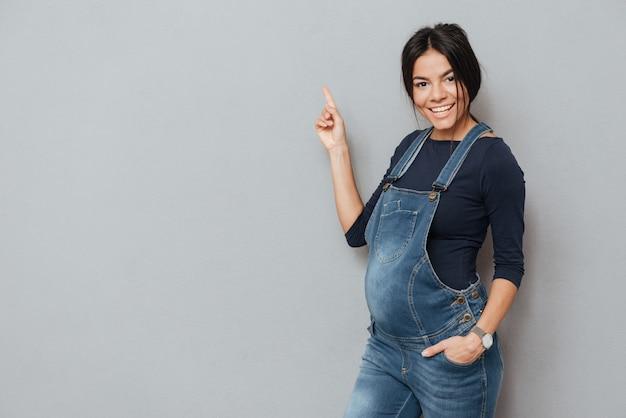 Счастливая беременная женщина, стоя над серой стеной и указывая