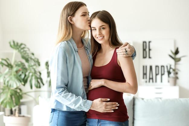 집에서 행복한 임신한 레즈비언 커플