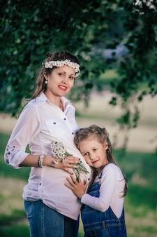 여름날 산책을 위해 어린 딸과 함께 행복한 임신한 엄마. 좋은 시간