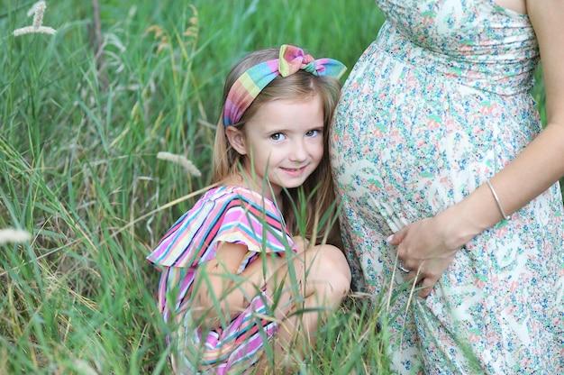 幸せな妊娠中の女性と彼女の娘が夏の公園でポーズ