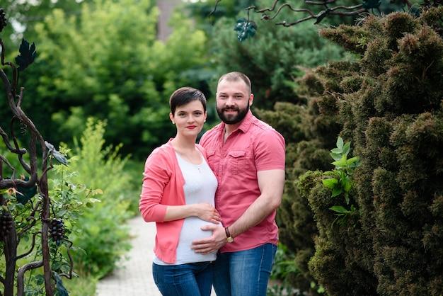 Счастливая беременная женщина и ее муж в парке